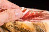 Caucasian man hand takes slices from Serrano ham — Stock Photo