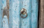 Old run-down blue painted wooden door nails — Stock Photo