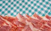 Top view of Serrano ham slices over plate and tablecloth — Stock Photo