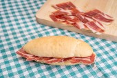 Side view of Serrano ham sandwich over checkered tablecloth — Stock Photo