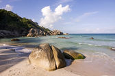 Tropical beach with stones and incoming waves — Stock Photo