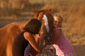 Mother and daughter feeding her handsome horse — Stock Photo