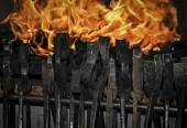 Smith tongs in the fire background — Stock Photo