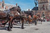 Brügge, belgien - 12. juni 2014: die beförderung auf dem grote markt und belfort van brugge im hintergrund. — Stockfoto