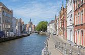 BRUGES, BELGIUM - JUNE 13, 2014: Typically house over the canal from Sint Annarei street and st. Giles church in the background. — Stock Photo