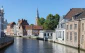 BRUGES, BELGIUM - JUNE 12, 2014: Typically house over the canal from Sint Annarei street with the st. Ann church in the background. — Stock Photo