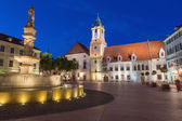 BRATISLAVA, SLOVAKIA - SEPTEMBER 21, 2014: Main square in evening dusk with the town hall and Jesuits church. — Stock Photo