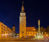 TRNAVA, SLOVAKIA - OCTOBER 14, 2014: The Main square with the bell-tower and the holy Trinity baroque column at dusk. — Stock Photo