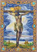 SEVILLE, SPAIN - OCTOBER 28, 2014: The ceramic tiled Crucifixion by Ramos Resano on the facade of church Iglesia de San Pedro by Akiernam in manufactory Ceramica Santa Ana de Triana (1952). — 图库照片
