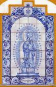 SEVILLE, SPAIN - OCTOBER 29, 2014: The ceramic tiled Madonna of Rosary on the facade of chapel Capilla dos de Mayo by R. A. Mejias and J. L. Aguado from 20. cent. — Stock Photo