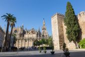 SEVILLE, SPAIN - OCTOBER 28, 2014: Cathedral de Santa Maria de la Sede with the Giralda bell tower and walls of Alcazar. — Stock Photo