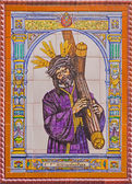 """SEVILLE, SPAIN - OCTOBER 29, 2014: The ceramic tiled Christ with the cross by manufactory """"Campos"""" from Seville on the church facade. — Foto de Stock"""