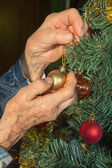 Hands of old woman and christmas decoration — Stock Photo