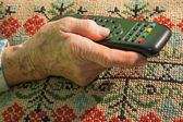 Hand of old woman with TV driver — Stock Photo
