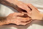 Hands of grandmother and grandchild in the bed — Stock Photo