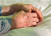 Hands of old woman on the bed — Stock Photo