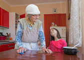 Hands of grandmother and grandchilds in the kitchen — Stock Photo