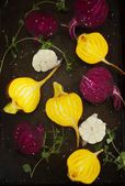 Preparing raw beetroots and garlic for roasting on a baking tray — Stock Photo