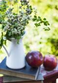 Summer wild flowers in glass vase, old books and apples. — Stock Photo
