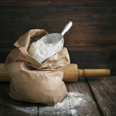 Flour in paper bag on wooden background. — Stock Photo