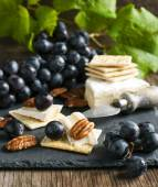 Delicious cheese crackers appetizer with grapes and pecans — Stock Photo