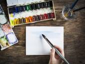 Hand with paintbrush. Painting with watercolor. Selective focus — Stock Photo