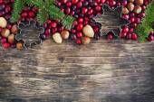 Christmas border with cranberries, spruce branch and cookie cutters — Stock Photo