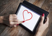 Young girl draws heart on the tablet — Stock Photo
