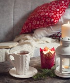 Still life interior details, cup of tea, candles near the sofa with pillows — Stock Photo