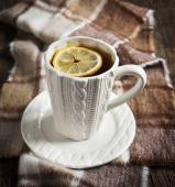 Cup of hot tea with lemon and scarf on wooden table — Stock Photo