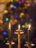 Burning candles on blurring Christmas lights background — Stock Photo