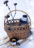 Basket with thermos of mulled wine and knitted blanket on sledge — Stock Photo