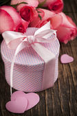 Bouquet of pink roses and gift box on wooden background — Foto de Stock