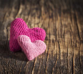 Two crochet pink hearts on wooden background — Stock Photo