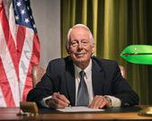 Presidente jefe escribiendo detrás de escritorio con la bandera americana en el — Foto de Stock