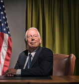 Big boss president sitting behind desk with american flag in the — Stock Photo