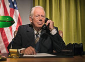 Big boss president calling behind desk with american flag in the — Stock Photo