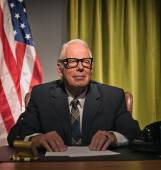 Big boss president wearing glasses sitting behind desk with amer — Stock Photo
