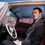 Retro 60s fashion business man wearing grey suit with tie sittin — Stock Photo #52631965