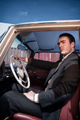 Retro 60s fashion business man wearing grey suit with tie sittin — Stock Photo