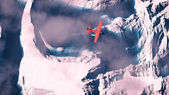 Aerial of red airplane flying over arctic snow landscape with bl — Stok fotoğraf