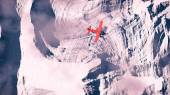 Aerial of red airplane flying over arctic snow landscape. — Stok fotoğraf