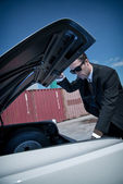 Retro fifties mafia fashion man looking in trunk of vintage car. — Stock Photo