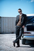 Retro fifties mafia fashion man standing next to open trunk of v — Stock Photo