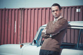 Retro fifties business fashion man leaning against vintage car. — Stock Photo