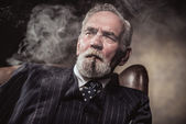 In chair sitting characteristic senior business man. Smoking cig — Stok fotoğraf