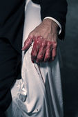 Bloody hand of businessman sitting in white chair. — Stock Photo