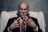 Bad businessman with bloody hands sitting in white chair. Gray b — Stock Photo