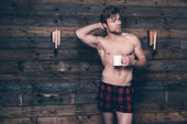 Man with blonde hair and bare chest wearing red flannel shorts.  — Stock Photo