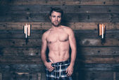 Man with blonde hair and bare chest wearing blue flannel pants.  — Stock Photo